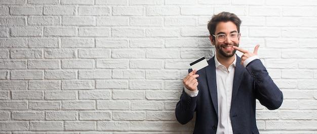 Jonge zakenman draagt een pak tegen een witte bakstenen muur glimlacht