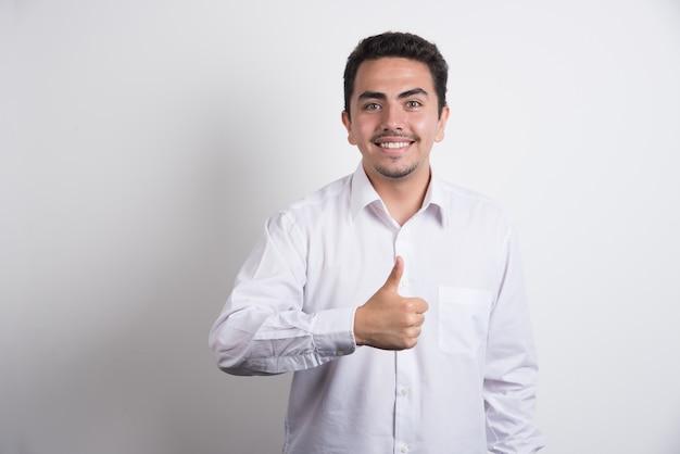 Jonge zakenman duimen opdagen op witte achtergrond.