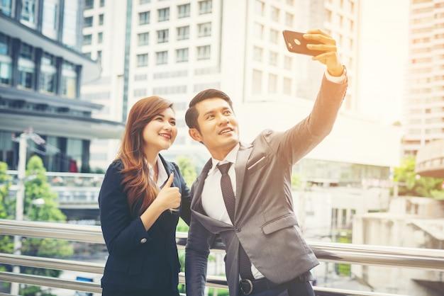 Jonge zakenman en collega buitenshuis in stedelijke omgeving nemen een selfie