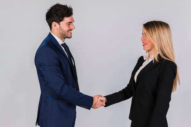 Jonge zakenman en onderneemster die elkaars hand schudden tegen grijze achtergrond