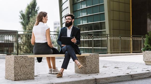 Jonge zakenman en onderneemsterzitting op bank buiten het bureaugebouw