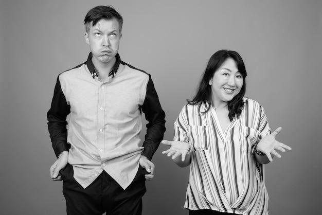 Jonge zakenman en rijpe japanse onderneemster samen tegen grijs in zwart-wit