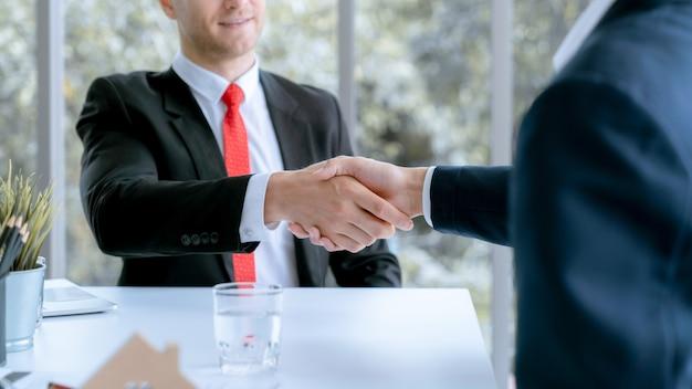 Jonge zakenman en thuisklantklant hadden samen doelmiddelen bereikt en in het verkoopcontract getekend.