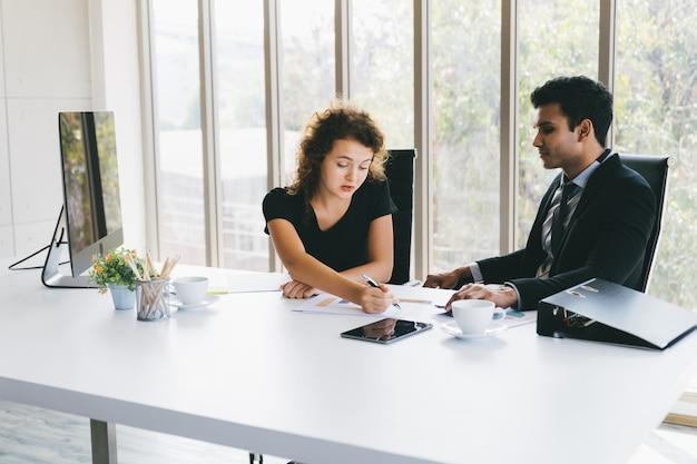Jonge zakenman en vrouw die over zaken op gegevensbladen in huisbureau bespreken