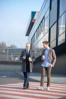 Jonge zakenman en zijn volwassen mentor die de straat oversteken met een pauze op het werk