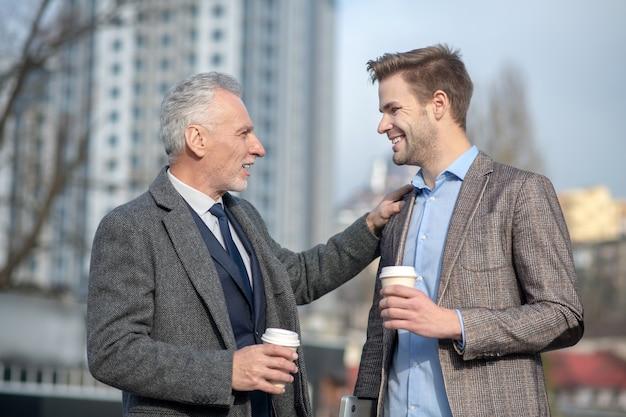 Jonge zakenman en zijn volwassen mentor glimlachen tijdens een gesprek