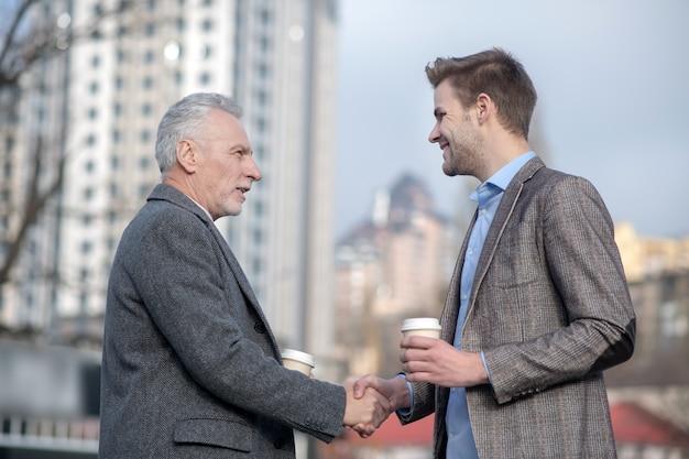 Jonge zakenman en zijn volwassen mentor handen schudden terwijl ze op straat staan