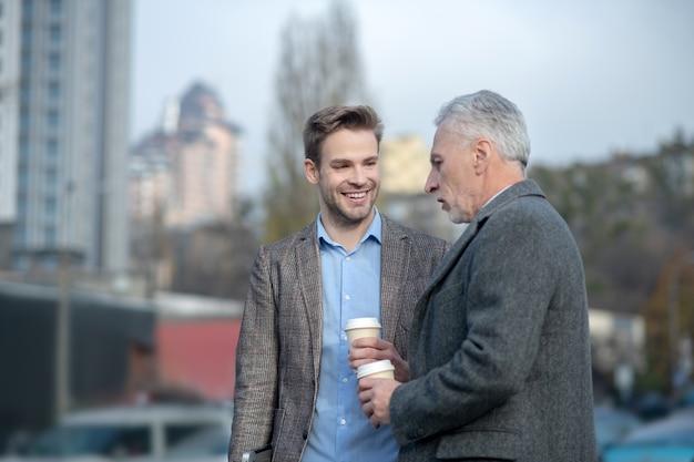 Jonge zakenman en zijn volwassen mentor met een gesprek in de buurt van het kantoor