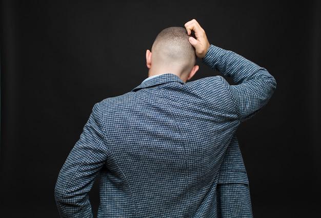 Jonge zakenman gevoel clueless en verward, denkend een oplossing, met hand op heup en andere op hoofd, achtermening tegen vlakke muur