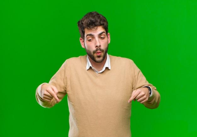 Jonge zakenman gevoel geschokt, met open mond en verbaasd, kijkend en naar beneden wijzend in ongeloof en verbazing tegen groen