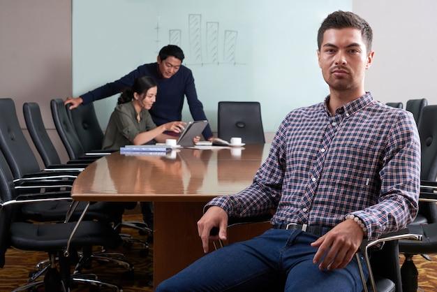 Jonge zakenman gezet als bureauvoorzitter die camera bekijkt