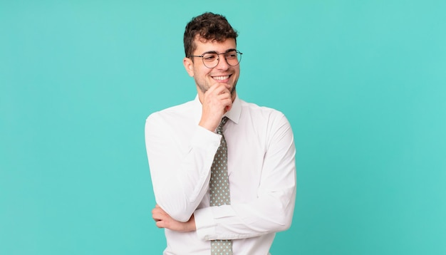 Jonge zakenman glimlachend met een gelukkige, zelfverzekerde uitdrukking met de hand op de kin, zich afvragend en opzij kijkend