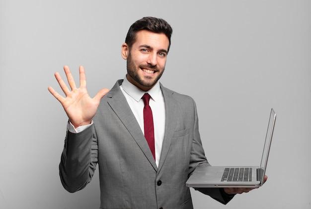 Jonge zakenman glimlacht en ziet er vriendelijk uit, met nummer vijf of vijfde met hand naar voren