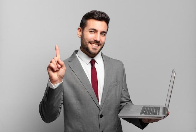 Jonge zakenman glimlacht en ziet er vriendelijk uit, toont nummer één of eerst met de hand naar voren, telt af en houdt een laptop vast