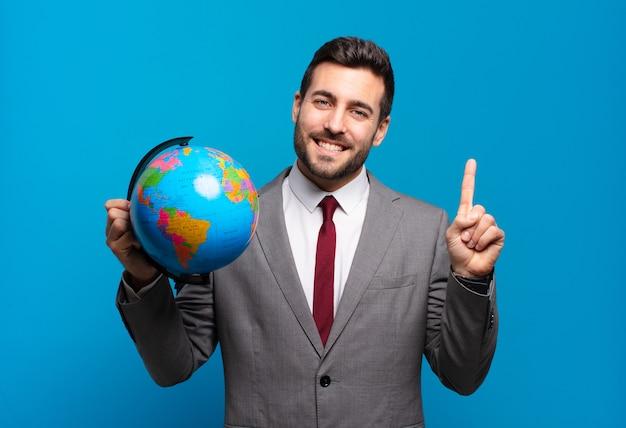 Jonge zakenman glimlacht en ziet er vriendelijk uit, toont nummer één of eerste met hand naar voren, aftellend met een wereldbolkaart