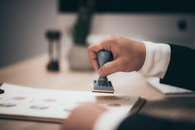 Jonge zakenman goedkeuring stamper stempel op papier zakelijk contract, lening geld goedgekeurd.
