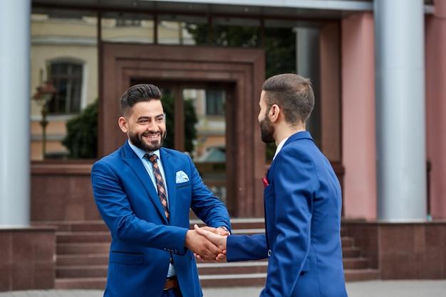 Jonge zakenman handenschudden met zijn zakenpartner buitenshuis glimlachend vreugdevol