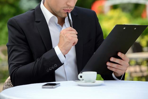 Jonge zakenman het drinken koffie terwijl het zitten in een koffie.