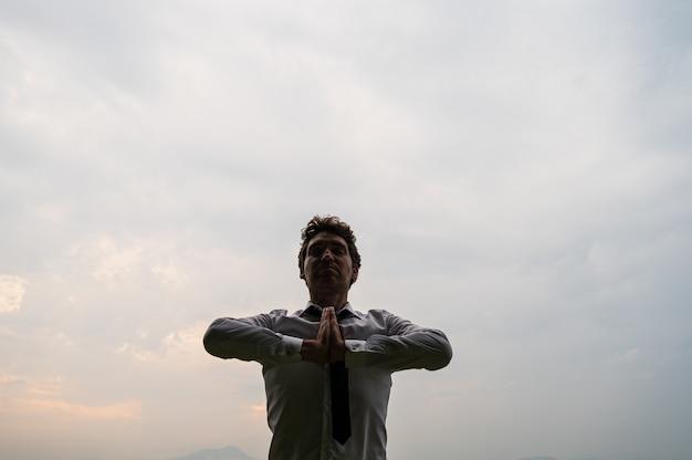 Jonge zakenman houdt zijn handen samen op zijn borst terwijl hij mediteert onder bewolkte hemel.