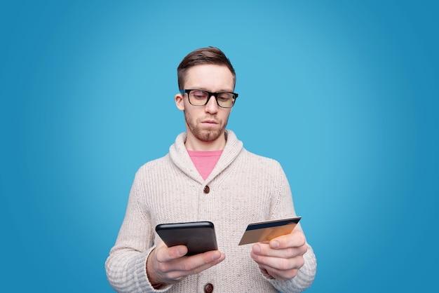 Jonge zakenman in bril met behulp van smartphone tijdens het maken van online bestelling en het aantal plastic kaart afzonderlijk invoeren