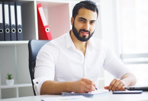 Jonge zakenman in bureau dat aan computer werkt