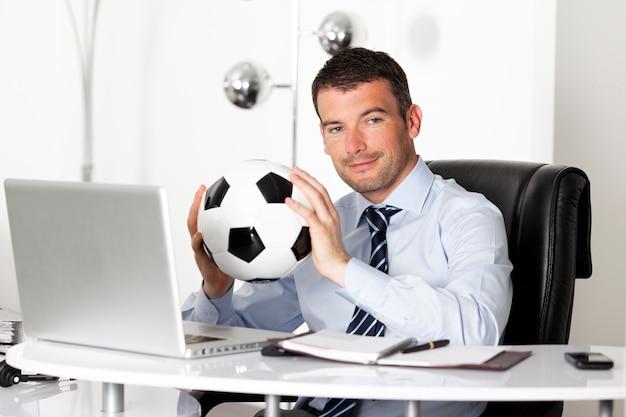 Jonge zakenman in bureau met computer en bal