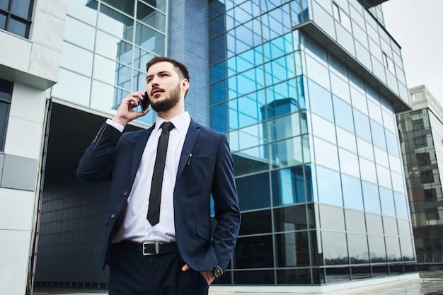 Jonge zakenman in een blauw kostuum die op een celtelefoon spreken op de achtergrond van een glas bedrijfsgebouw
