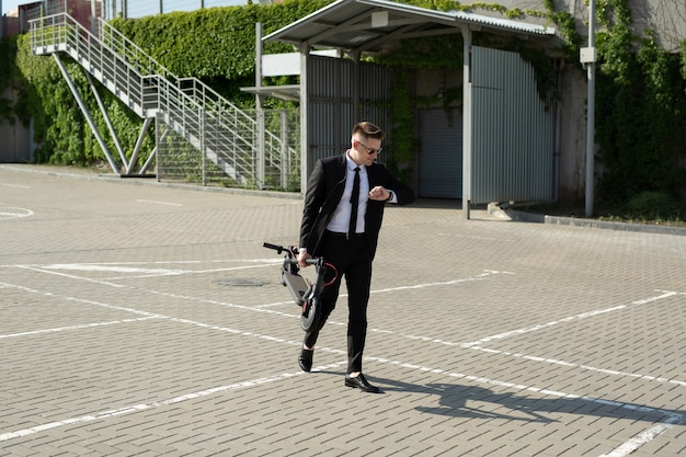 Jonge zakenman in een pak kijkt naar zijn horloge en draagt een elektrische scooter in zijn handen