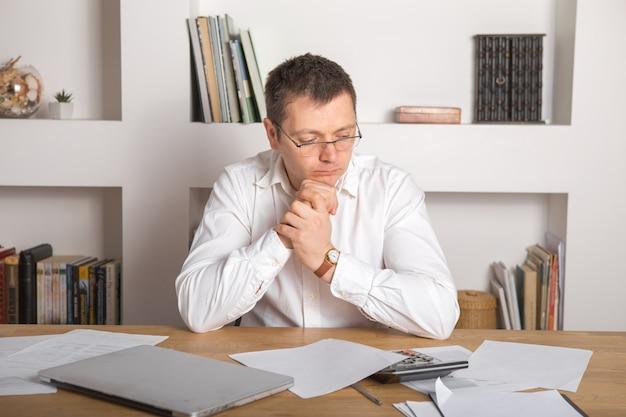 Jonge zakenman in een werkplek met verrassing en geschokte gelaatsuitdrukking