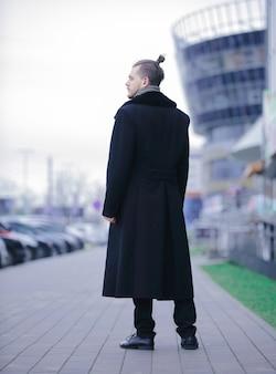 Jonge zakenman in een winterjas die op straat staat. foto met kopieerruimte