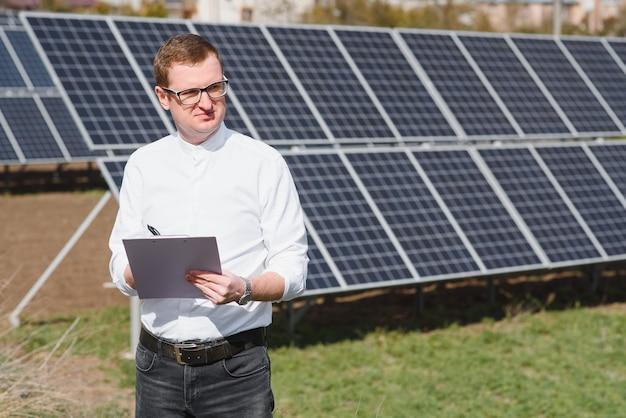 Jonge zakenman in een wit overhemd in de buurt van de zonnepanelen voor elektriciteitscentrales