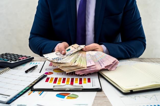 Jonge zakenman in functie telt geld als winst na een succesvolle deal. de man vergelijkt en wijst naar winst. zakelijke grafieken, oekraïens hryvnia-geld op tafel.