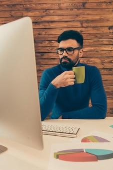 Jonge zakenman in glazen koffie drinken tijdens het werken op pc