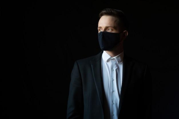 Jonge zakenman in klassiek kostuum die een beschermend medisch geïsoleerd gezichtsmasker dragen
