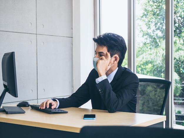 Jonge zakenman in pak dragen van beschermend gezichtsmasker werken op de computer en denken met spanning met moe gezicht met smartphone op bureau in kantoor in de buurt van groot glazen raam.