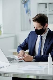 Jonge zakenman in pak en gezichtsmasker aan bureau zitten en laptop met natte servet in kantoor desinfecteren