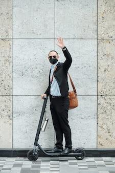 Jonge zakenman in pak en medisch masker rijden op scooter en zwaaien