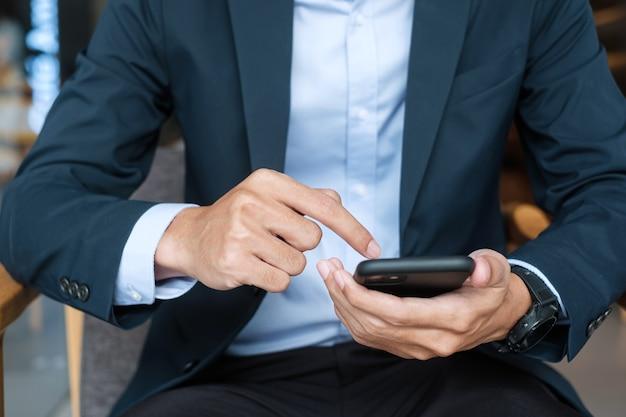 Jonge zakenman in pak houden en het gebruik van smartphone voor sms-berichten, man touchscreen mobiele telefoon typen in kantoor of café. zaken, levensstijl, technologie en social media netwerkconcept