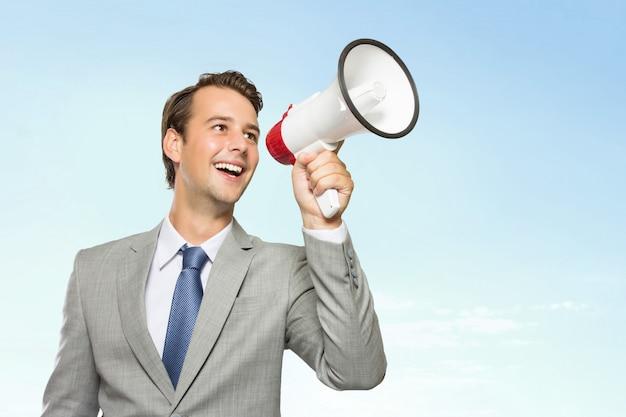 Jonge zakenman in pak met een megafoon in zijn hand, glimlachend