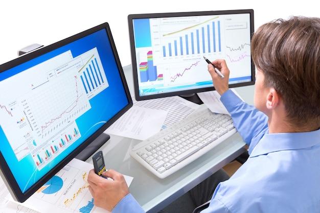 Jonge zakenman in pak met twee computers voor werk