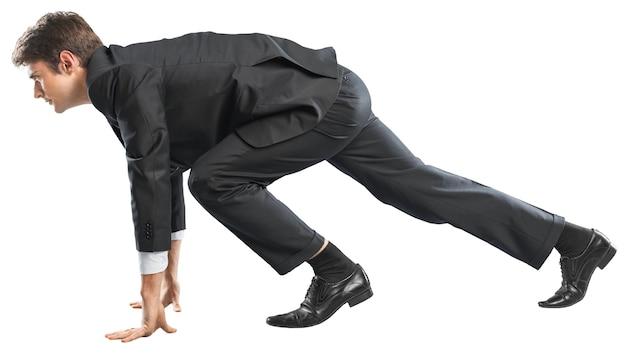 Jonge zakenman in start pose voor hardlopen geïsoleerd op wit