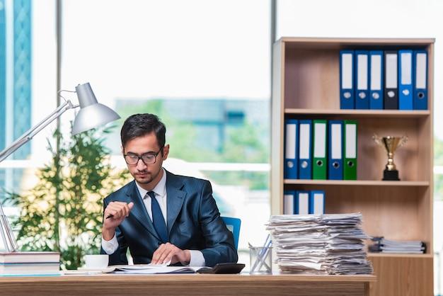 Jonge zakenman in stress met veel papierwerk