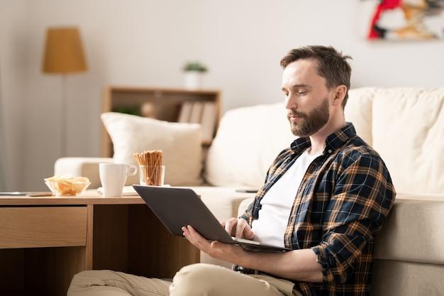 Jonge zakenman in vrijetijdskleding die zich op het bladeren in het net concentreert en naar informatie zoekt terwijl hij thuis werkt