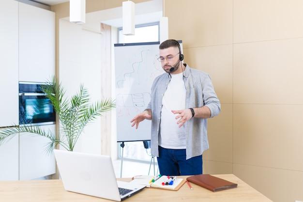 Jonge zakenman in vrijetijdskleding met een hoofdtelefoon online vergaderingspresentatie of training met behulp van een laptop, webcam en een flip-over