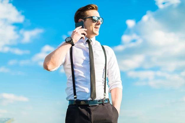Jonge zakenman in wit overhemd, stropdas, bretels en zonnebril staan op de dakladder