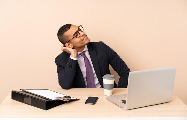 Jonge zakenman in zijn kantoor met een laptop en andere documenten denken een idee