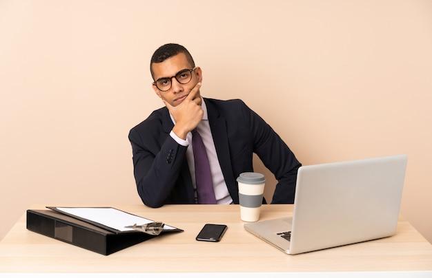 Jonge zakenman in zijn kantoor met een laptop en andere documenten denken