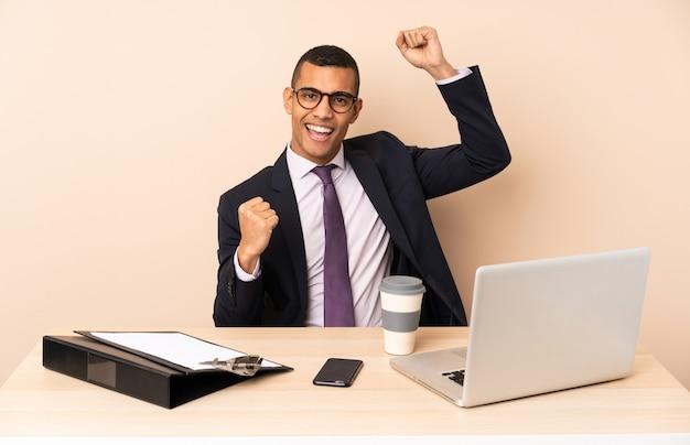 Jonge zakenman in zijn kantoor met een laptop en andere documenten die een overwinning vieren