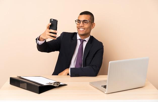 Jonge zakenman in zijn kantoor met een laptop en andere documenten die een selfie maken