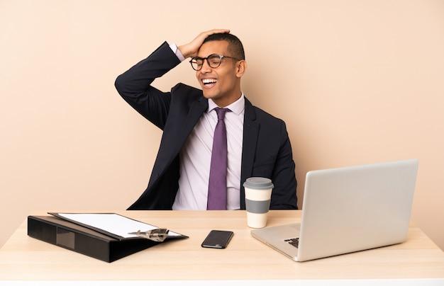 Jonge zakenman in zijn kantoor met een laptop en andere documenten die veel glimlachen